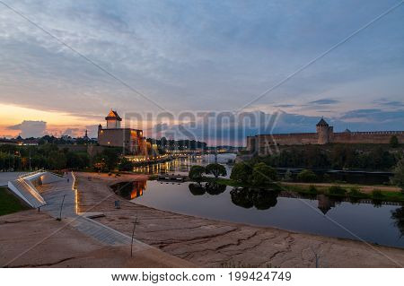 Opposition of two medieval fortresses on the river Narva at sunset, Estonia and Russia border