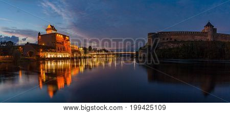 Opposition of two medieval fortresses on the river Narva at blue hour, Estonia and Russia border. Wide panoramic view