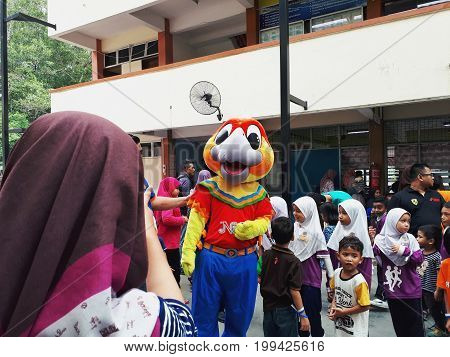 SHAH ALAM, MALAYSIA - AUGUST 12, 2017: Crowds of peoples with mascost and an artist during BREAK THE COIN BOX AND COLORING CONTEST yearly event sponsored by BANK RAKYAT.