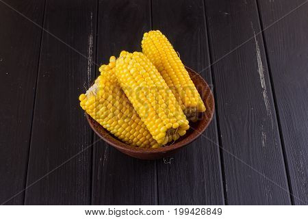 Boiled corn in a bowl on a black wooden background