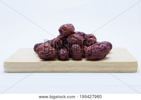 Red chinese dried jujube on wooden board on white background