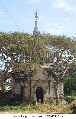 Ancient Buddhist pagoda among trees on a sunny day. Bagan, Burma