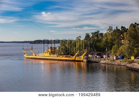 VAXHOLM, SWEDEN - SEPTEMBER 15, 2016: Small yellow Ro-Ro ferry goes near medieval Oscar Fredriksborgs fortification. Landmarks of Stockholm archipelago