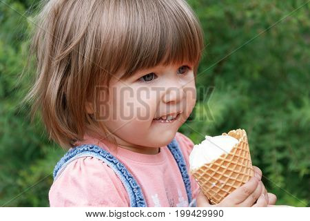 Horizontal photo of cute girl are eating icecream in summer time