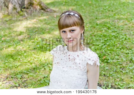 Beautiful bride in white dress sitting on the green grass