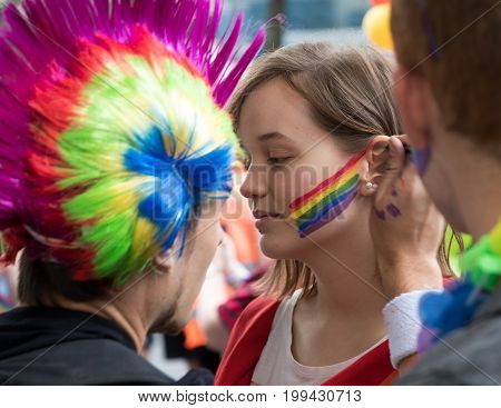 PRAGUE CZECH REPUBLIC - AUGUST 12 2017: Man painting a rainbow on a woman's face during Prague Pride - a big gay & lesbian pride