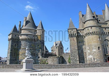 Statue in the square with Vitre Castle, France