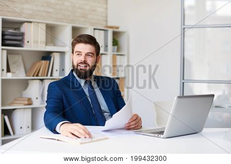 Portrait of successful  bearded businessman  smiling happily looking away while working at desk in modern office