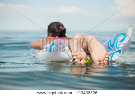 A girl is floating on an inflatable mattress in the Lake Baikal.