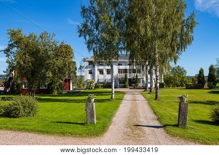 Farm house and road to it. White wooden cottage with trees. Hedemora, Sweden