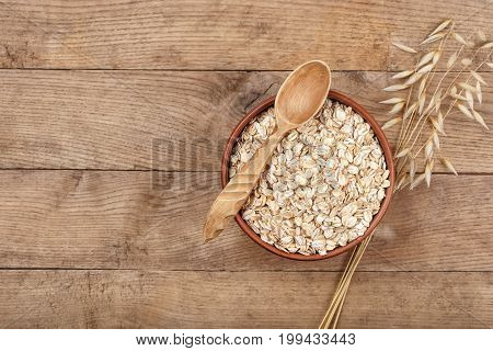 still life oat flakes in bowl and oat ear on wooden table top view. Uncooked oatmeal