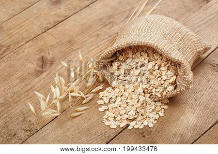 still life oatmeal in bag and oat ear on wooden table. Uncooked rolled oat flakes