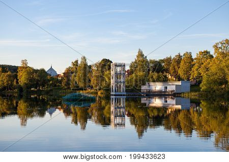 A traditional cottage and jumpring tower stands by the lakeside in Hedemora, Sweden