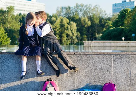 Boy tells the girls secrets from school children in clothes for school
