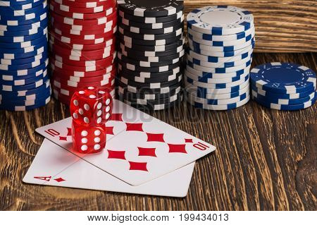 Poker cards with cubes are beautifully placed on the table against the background of poker chips