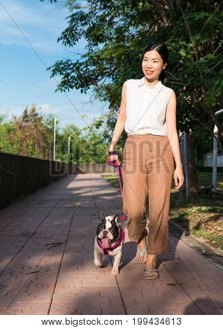 an Asian young woman walking in a public park with her french bulldog in a sunny day an activity for a dog and dog lover