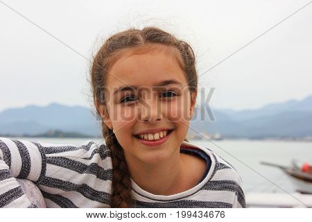 Smiling young girl sitting near by sea in Fethiye harbour