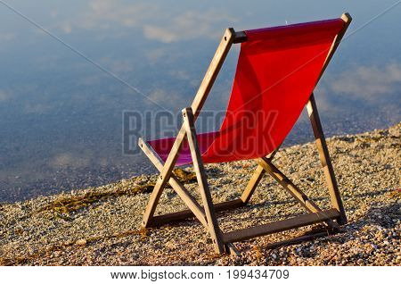 Red chair on a bank of Ada lake with cloud reflections in a water at summer morning, Belgrade, Serbia