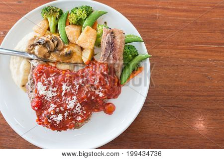 top view of pork chop steak with red tomato sauce one of delicious meat menu