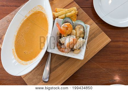 seafood soup with shrimp mussel squid and scallops served on the wood table. Delicious appetizer for main course