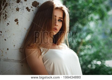 Stylish girl model with long hair posing on a sunny day