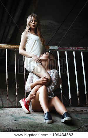 A pair of stylish models girls with long hair posing passionately on a sunny day under a bridge in an abandoned place