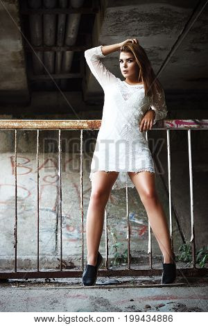 Stylish girl model with long hair posing on a sunny day under a bridge in an abandoned place