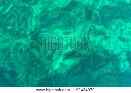 White sand sea floor 10m deep, partly visible through crystal clear turqoise water of Aegean sea, near Orange beach, Sithonia, Greece