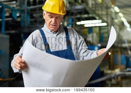 Portrait of senior man looking at floor plans in workshop of modern factory
