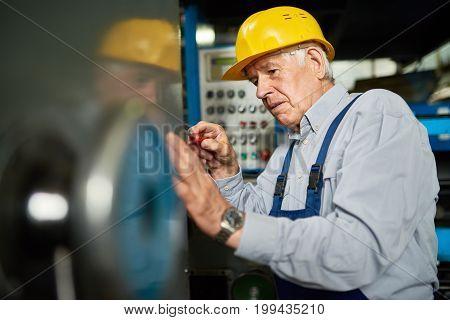 Portrait of senior mechanic repairing machine units in workshop of modern factory