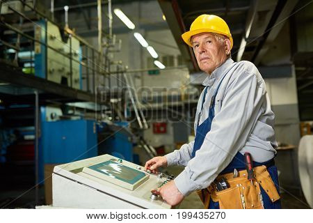 Portrait of senior man operating machine units in modern factory standing by control panel and looking away