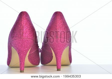 Pink glittery high heals party shoes from the behind, Close up, copy space. White background