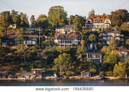 View on luxury cottages with private embankment along Stockholm archipelago, Sweden. Summer sunset time.