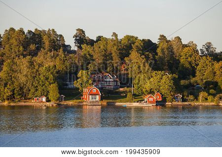 View on luxury cottages with private beach along Stockholm archipelago, Sweden. Summer sunset time.