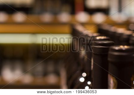 perspective view closeup of row red wine bottles in supermarket shelf with selective focus