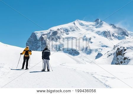 two people are trekking on the snow mountain in a sunny day in Switzerland happy trip for tourists
