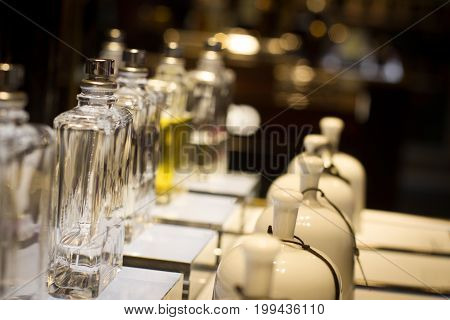 perspective view of white ceramic fragrance bells and perfume bottles in store shelf display with selective focus