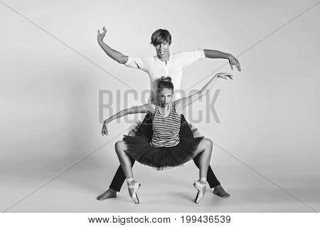 beautiful ballet couple. ballerina in black tutu skirt. man in jeans and white shirt. studio shot. copy space.
