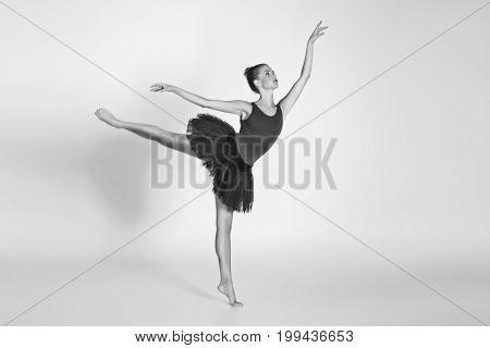 beautiful ballet couple. ballerina in black tutu skirt. man in jeans and white shirt. studio shot. copy space.