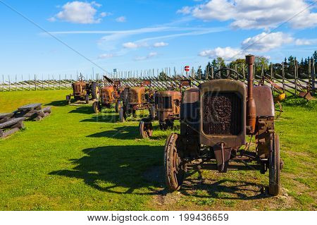 Rusty vintage tractors in the field. Museum installation.