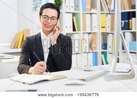 Attractive middle-aged designer writing down order details while talking to her client on mobile phone, interior of modern office on background
