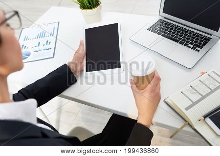 Over shoulder view confident white collar worker enjoying fragrant coffee while preparing annual accounts on digital tablet