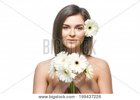 beautiful young woman with natural makeup and straight hair holding white Herberas flowers. beauty shot isolated on white background. copy space.
