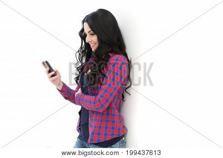 Beautiful Cute Girl In A Checkered Shirt Standing Near A White Wall And Dials Sms Or Internet Use.