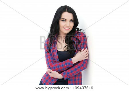 Young Beautiful Curly Woman In Plaid Shirt Posing On Gray Background