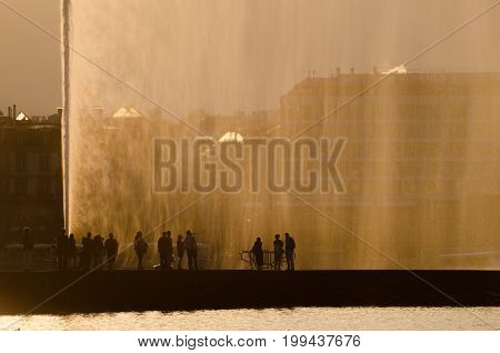 People silhouette on Jet d'Eau - large fountain in Geneva on sunset time. Switzerland