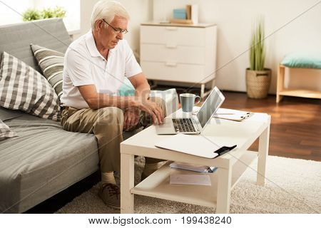 Portrait of modern senior man using laptop at home, working in retirement sitting on sofa in cozy living room