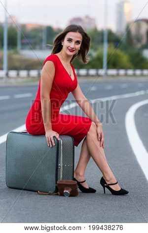 Beautiful young girl sits on a suitcase on the roadway
