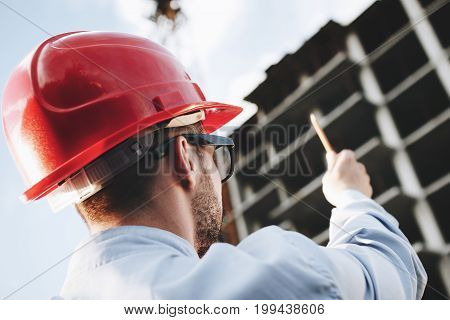 Inspector Inspects Construction Of Skyscraper. Male Engineer Or Safety Officer In Red Hard Hat On Ba