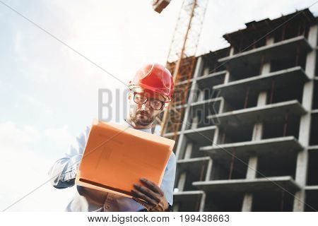 Man Architect In Construction Helmet And Glasses Looks At The Building Under Construction. Builder W